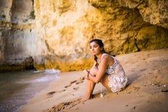 Het denken alleen voelt de Latijnse meisjeszitting op zand bij strand en het bekijken oceaan De zomerroeping Royalty-vrije Stock Fotografie