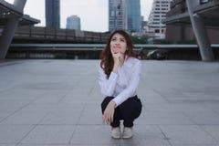Het denken en nadenkend bedrijfsconcept Portret van aantrekkelijke jonge Aziatische onderneemster zeker en glimlach die stedelijk royalty-vrije stock foto's