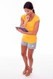 Het denken jong brunette met een tabletpc Stock Foto