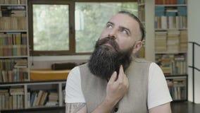 Het denken reactie van een mens die omhoog aan celling kijkt en vingers zijn baard doorneemt - stock video