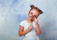 Het denkende meisje van het pretjonge geitje in gelukkig en glazen die eyegl kijken houden royalty-vrije stock fotografie