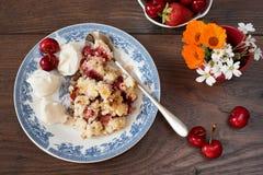 Het dessert van de kersenkruimeltaart met aardbeien en de vanille romen af, gediend op een blauwe plaat Kersen, aardbeien, bloeme royalty-vrije stock fotografie