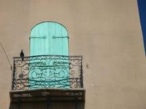 Het detail van een Ijzer verfraaide balkon met een gesloten houten groen venster en een vogel gezet op de rand van het balkon Royalty-vrije Stock Afbeeldingen