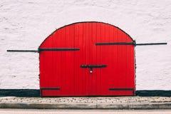 Het detail van een oude schuur rode deur met zwart metaal voorziet tegen een witte muur van een scharnier Royalty-vrije Stock Foto's