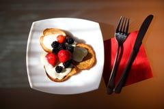 Het detail van eigengemaakte pannekoeken met yoghurt, esdoornstroop en vruchten Stock Foto
