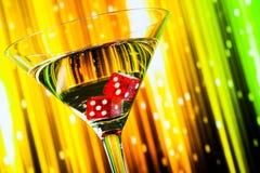 Het detail van rood dobbelt in het cocktailglas op kleurrijke gradiënt Stock Afbeeldingen