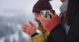 Het detailsportret van jonge toerist twee drinkt wat hete thee, in verbazende de winterplaats in de bovenkant van berg met sneeuw stock video