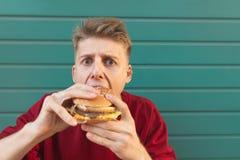 Het dichte portret van een jonge mens die een hamburger eet bekijkt de camera tegen de achtergrond van een turkooise muur royalty-vrije stock foto