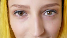 Het dichte portret van ogen van vrouw met geel haar, opent ogen, ongebruikelijke persoon die bij camera staren, intens en geconce stock videobeelden