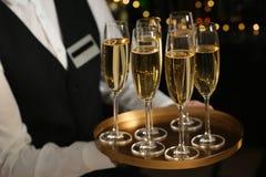 Het dienblad van de kelnersholding met glazen champagne op vage achtergrond stock afbeelding
