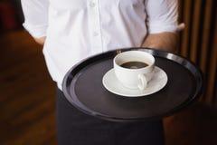 Het dienblad van de kelnersholding met koffiekop Stock Foto