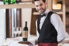 Het dienblad van de kelnersholding met wijnglazen en fles Stock Foto