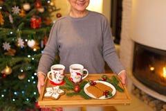 Het dienblad van de vrouwenholding van Kerstmiskoekjes royalty-vrije stock fotografie