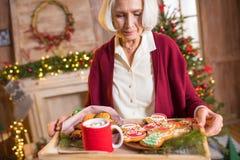 Het dienblad van de vrouwenholding met Kerstmiskoekjes Stock Fotografie