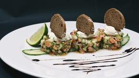 Het dienen van een salade met kalk en brood in een witte plaat op een zwarte achtergrond in 4k-resolutie met diacamera stock footage