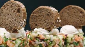 Het dienen van een salade met kalk en brood in een witte plaat op een zwarte achtergrond in 4k-resolutie met diacamera stock videobeelden