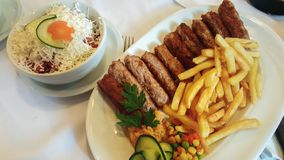 Het dienen van kebabs met gebraden aardappels en groenten in een plaat Kippensalade, groenten en kaas royalty-vrije stock afbeeldingen