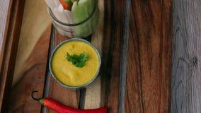 Het dienen van oranje onderdompelingssaus met plantaardige stokken op dienblad Hoogste mening Het eten van veganist en vegeterian stock video
