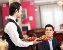 Het dienende overzeese voedsel van de kelner Stock Fotografie