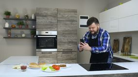 Het dikke gebaarde mannetje neemt een foto van voedsel gebruikend een telefoon in een moderne keuken, alvorens een eigengemaakte  stock videobeelden