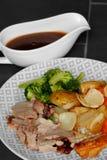 Het diner van het varkensvleesbraadstuk met groenten en jus stock afbeeldingen