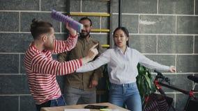 Het diverse multi-etnische start commerciële team heeft pret dansend in zolderbureau en het vieren succes van project