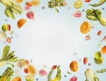 Het diverse vliegen of dalende de zomervruchten, bessen en groenten op lichtblauwe achtergrond, kader Gezond detoxvoedsel stock afbeeldingen