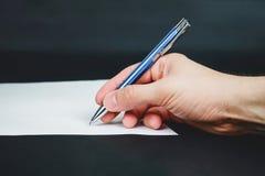 Het document en de hand van het persoonsteken houden blauwe pen op donkere achtergrond Stock Afbeelding