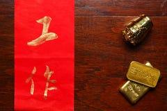 Het document schreef Chinese tekstbetekenis van goede wens naast plastic oude Chinese gouden barscène royalty-vrije stock fotografie