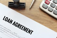 Het document van de leningsovereenkomst met rubberzegel en calculator op hout Royalty-vrije Stock Afbeelding