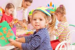 Het document van de meisjeslijm in het bewerken van kleuterschool royalty-vrije stock afbeelding