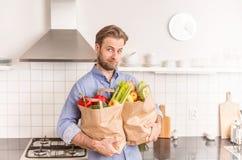 Het document van de mensenholding kruidenierswinkel het winkelen zakken in de keuken royalty-vrije stock foto's