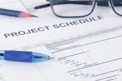 Het document van het projectprogramma met pen, potlood, eyeglases en gantt grafiek stock afbeeldingen