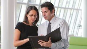 Het Document van zakenmanand businesswomen discussing stock footage