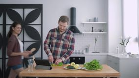 Het doel om gewicht te verliezen, gelukkig wijfje met mannetje bereidt gezonde maaltijd van groenten en greens volgens dieetplan  stock footage