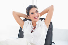 Het doen leunen onderneemsterzitting bij haar bureau die bij camera glimlachen Royalty-vrije Stock Afbeeldingen