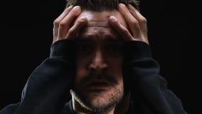 Het doen schrikken hoofd van de mensenholding tegen donkere achtergrond, psychologische ziekte, close-up stock video