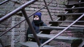 Het doen schrikken mannelijke tiener verbergen achter de oude baksteenbouw, die uit voorzichtig eruit zien stock footage