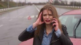 Het doen schrikken meisje spreken op de telefoon na een autoongeval in de regen, auto is gebroken stock footage
