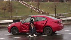 Het doen schrikken meisje spreken op de telefoon na een autoongeval in de regen, auto is gebroken stock videobeelden