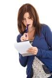 Het doen van de vrouw registreert het bijten pen Royalty-vrije Stock Afbeeldingen