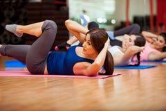 Het doen van kraken tijdens een gymnastiekklasse Stock Afbeelding
