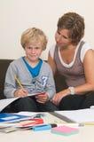 Het doen van thuiswerk met moeder stock afbeeldingen