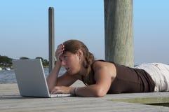 Het dok surfer meisje van de boot op verergerd Web stock foto's