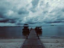Het dok van het botenstrand in de bewolkte dag stock afbeeldingen