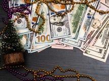 Het dollarsgeld die in Kerstmisspar vertakt leggen zich op de gebrande houten achtergrond van de raadsoppervlakte De decoratie va stock foto's