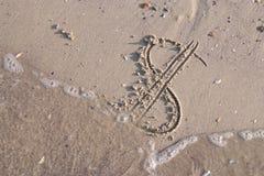 Het dollarteken op het zand van strand wordt geschilderd wordt gewassen weg door een overzees die stock fotografie