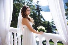 Het donker-haired, krullend-haired meisje bevindt zich op het balkon overziend de rivier, wordt een camera, gezet op a Stock Afbeelding