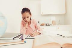 Het donker-haired Meisje doet Thuiswerk bij de Keuken royalty-vrije stock foto