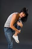 Het donker-haired meisje in jeans drukt linkerfoo Royalty-vrije Stock Foto's